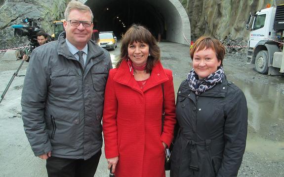 Foto av Noralv Distad, Jenny Følling og Dina Lefdal framfor Vangbergtunnelen mellom Olden og Innvik. Følling er kledd i raud kåpe, dei to andre i grå ytterjakkar. I bakgrunnen ser vi ei vegvesenbil og ein NRK-reporter med tv-kamera.
