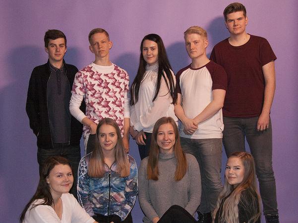 Foto av arrangørkomitten for Sogndal Filmfestival 2017. Ni ungdomar er fotograferte mot lilla bakgrunn, tre gutar og ei jente står i bakerste rekke, så sit det fire jenter fremst.