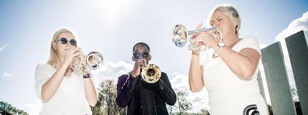Tre personar spelar trompet i sola.