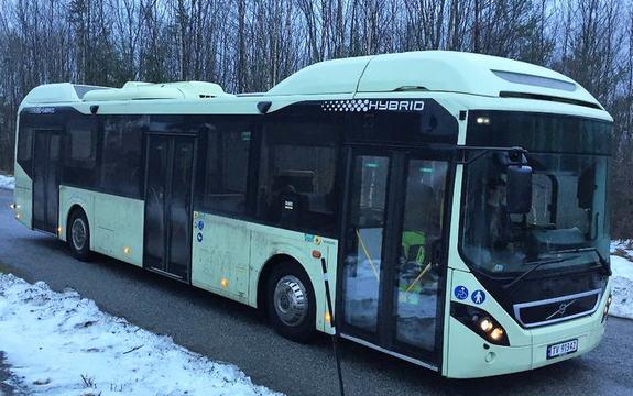 Foto av lysegrøn hybridbuss som er ute og køyrer i skumringa. Vegen er berr, men det ligg snø i grøfta.