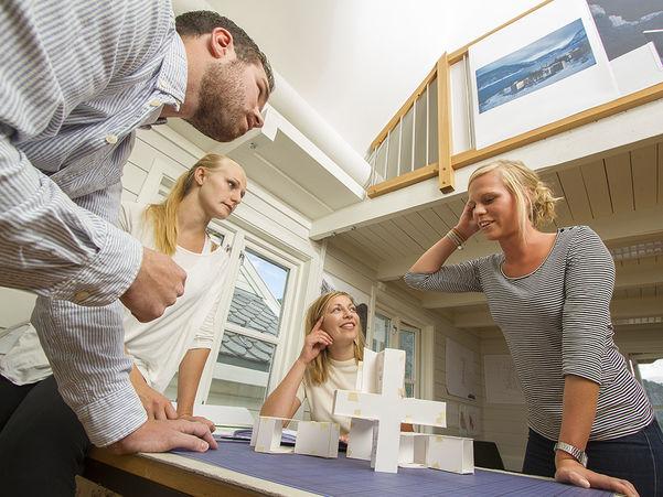 Foto som syner fire unge menneske rundt eit bord. Biletet er teke i bordhøgd og opp mot ansikta. To står ved bordet, ei sit ved bordet og ei sit på bordet. På bordet står det nokre figurar av papp.