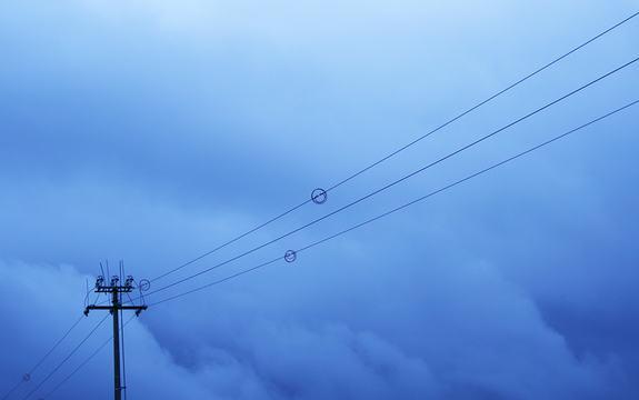 Foto av straumlinjer som går over ein overskya himmel i blåtimen. Vi ser masta til venstre i biletet og så går linjene oppover mot høgre.