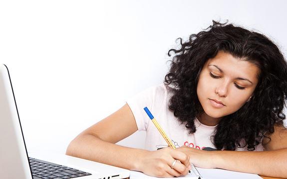 Foto av ei jente med brunt, krøllete hår som sit og noterer i ei notatblokk. Ved sidan av seg har ho ei kvit datamaskin.