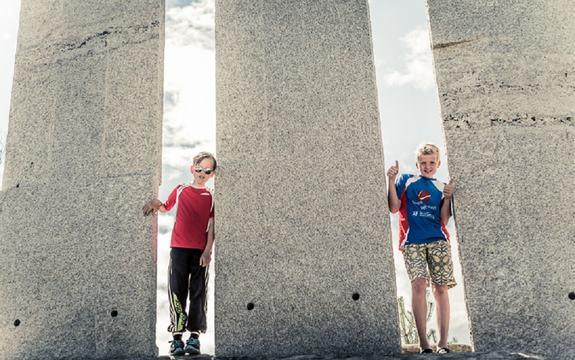 To barn står mellom statuane på Gulatinget.