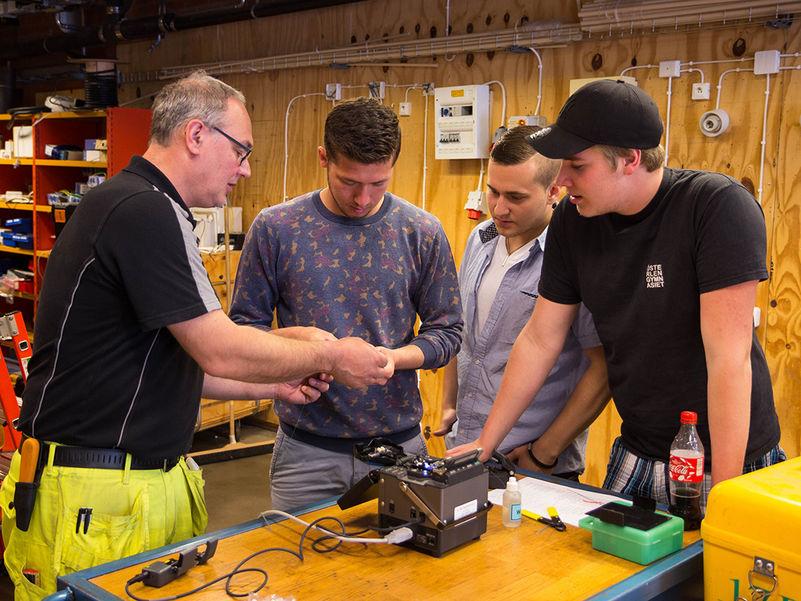 Foto av ein lærar og tre elevar eller lærlingar som står rundt eit bord og ser på noko elektronikk. Biletet er teke i ein slags verkstad, og læraren viser fram og forklarar.
