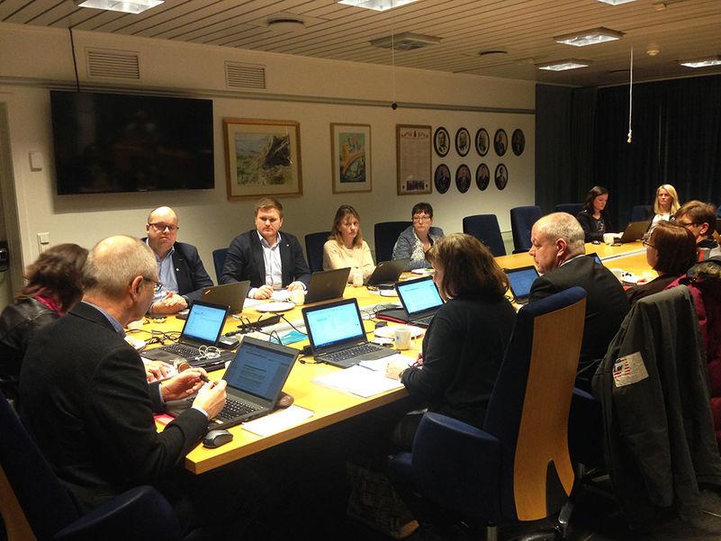 Foto frå møte i fylkesutvalet. Utvalet er samla rundt møtebordet, og alle har pc-ar framføre seg.