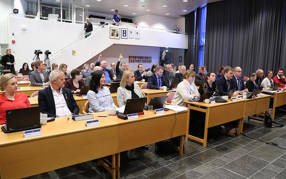 Foto av fylkestinget som røystar over intensjonsplanen for samanslåing med Hordaland. Vi ser tre representantar som stemmer imot, ved å halde oppe handa.