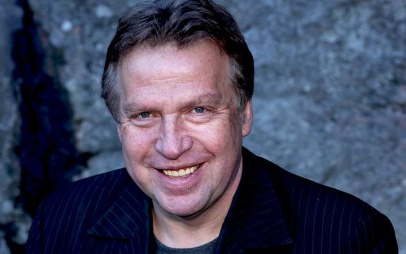 Portrettfoto av Erling Borgen. Han har på seg mørk dressjakke, ser rett i kameraet og smiler.