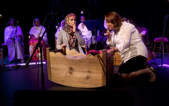 To kvinner syng voggesongar sittande ved sidan av ei vogge.