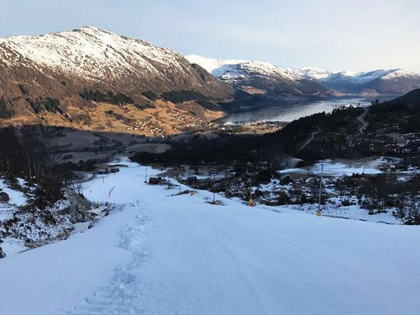Foto som syner skianlegget Jølster. Biletet er teke frå oppe i bakken og viser at det er snø berre i sjølve traseen. Det er usikt ned mot bygda og vatnet.