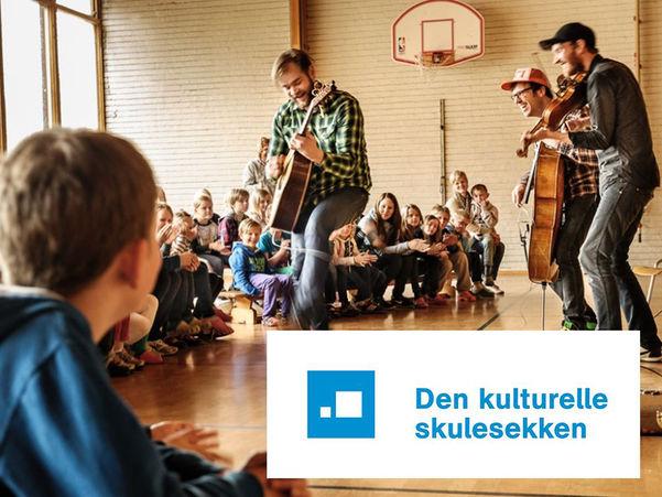 Foto frå førestilling i Den kulturelle skulesekken. Tre karar opptrer i ein gymsal med ungar rundt seg. Dei spelar gitar, fele og cello.