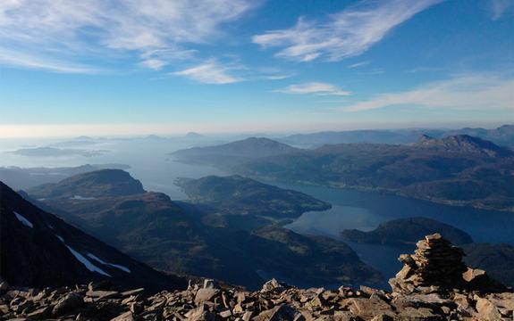 Foto av kystlandsskap teke frå ein fjelltopp. Vi ser utgangen av ein fjord, øyer og havet. I framgrunnen er det snaufjell med steinar og ein varde. Himmelen er blå med nokre småskyer.