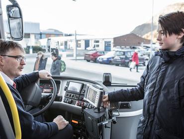 Foto av ein ung gut i samtale med ein bussjåfør på veg inn i bussen. Biletet er teke frå inni bussen og mot frontruta. Utanfor ser vi både bilar og folk på ein parkeringsplass.