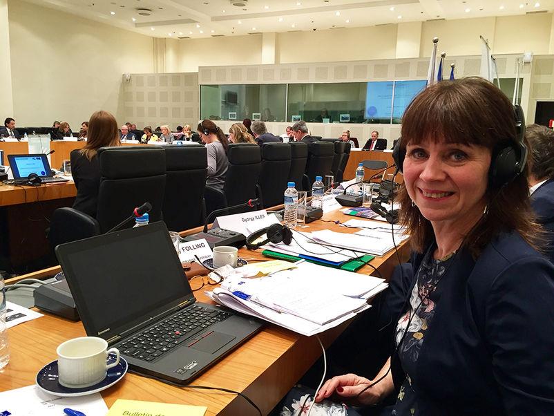 Foto av Jenny Følling på møte i Europarådet sin Congress Monitoring Committe. Biletet er frå møtesalen med mykje folk rundt. Følling ser i kameraet, har øyretelefonar på og pc og papir framføre seg på bordet.