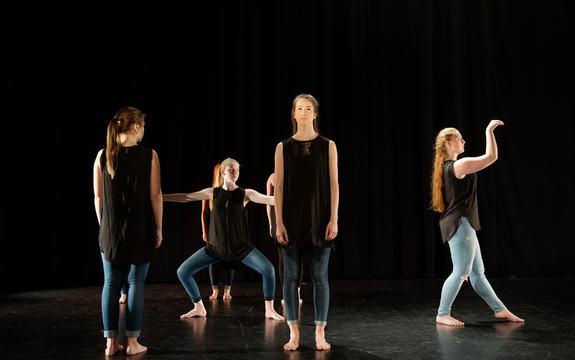 Seks jenter i jeans og svarte toppar dansar på ei scene.