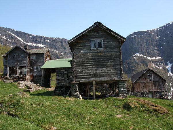 Foto av høgdegarden Ormelid i Luster. Biletet syner hovudhuset, fjøsen og stabburet ein sommardag. Graset er grønt, himmelen blå, og i bakgrunnen er det fjell med enkelte små snøflekkar.