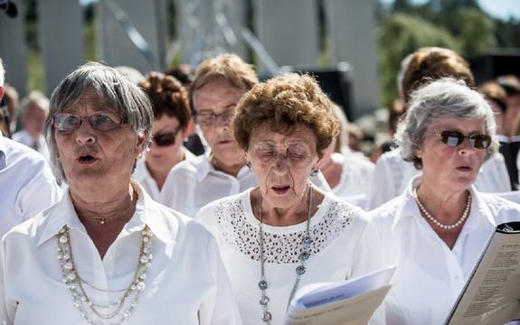 Eit kor med tre eldre kvinner i front syng på Gulatinget i samband med Grunnlovsjubileet i 2014.