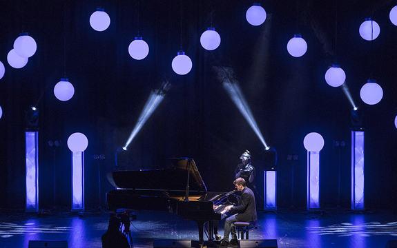 Foto frå UKM- Ung kultur møtest - festivalen 2016. Vi ser ein gut som spelar piano på ei scene, det er mørkt, men med lysprikkar over scena. Han blir filma av to ungdomar.