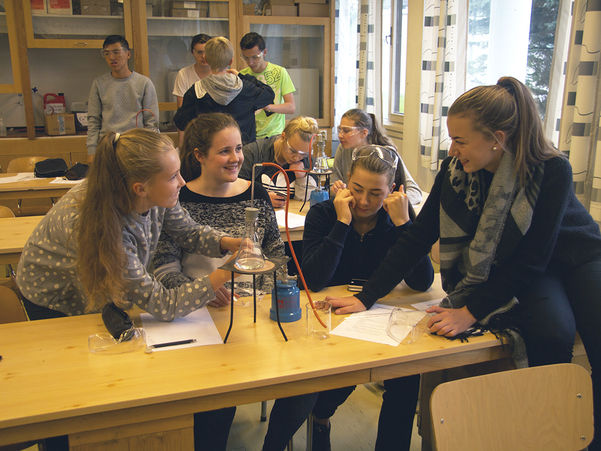Foto av elevar som sit i eit klasserom og driv på med noko eksperimentering med eit apparat på eit bord.