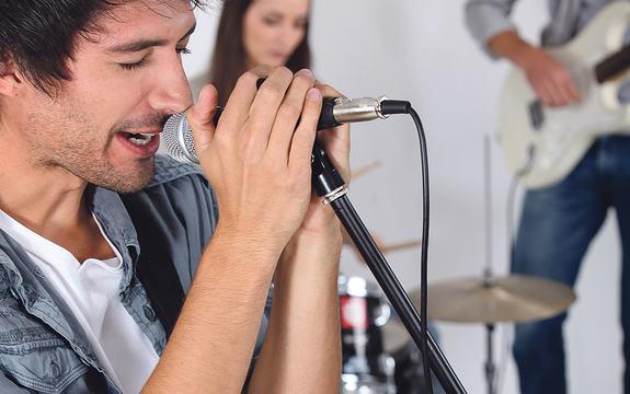 Band. Mann syng og spelar i gitar. I bakgrunnen spelar ei kvinne trommer og ein mann bass.