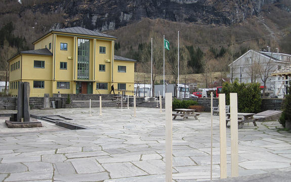 Foto som syner det gamle heradshuset i Stryn og plassen framfor, Per Bolstad plass. Det er laga til ei utstilling på plassen, med 50 like stativ bygde i tre. Stativa er smale og cirka 1,8 meter høge.