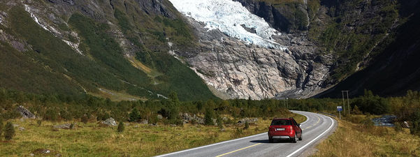 Foto som syner ein raud bil i Bøyadalen i Fjærland. Det er ein sommardag med sol. Vi ser Bøyabreen øvst i biletkanten.