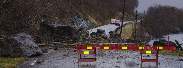 Foto som syner eit mindre steinras som er kome ned på bilvegen. Det ligg både store og mindre steinar og småbuskar i vegen. Det er sett opp ein sperring, og på andre sida av raset står det to bilar.