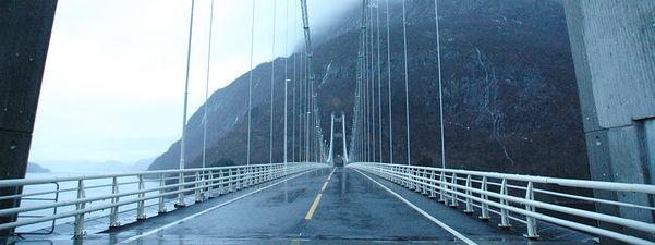 Foto frå Dalsfjordbrua. Det er overskya og grått, og det er ingen bilar på brua.