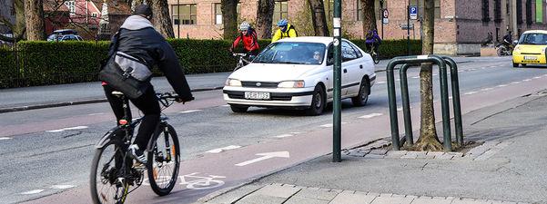 Foto som syner ein syklist som syklar i eit eige sykkelfelt i trafikken. Ein kvit bil kjem som møtande trafikk, og på andre sida av vegen kjem det to syklistar imot.