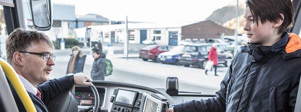Foto som syner ein bussjåfør og ein skuleelev i samtale når eleven er på veg inn på bussen. Bussen står parkert på ein parkeringsplass, og vi ser både folk og bilar utanfor bussen.
