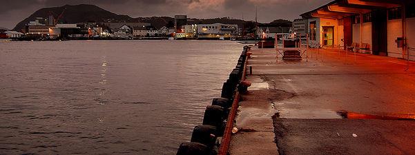 Foto som syner ein ferjekai i Florø i skumringa. Det er flott lys over byen, og vi ser noko av både sjø og by.