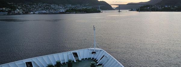 Foto frå dekket på ein båt som er på veg mot Måløybrua. Vi ser begge sidene av brua, sjøen er stille, og det er i skumringa.