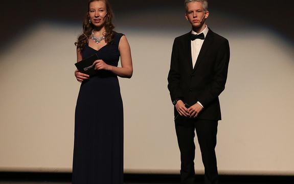 Foto som syner dei to konferansierane på Sogndal Filmfestival. Det er ei jente og ein gut, begge er gallakledde, ho i svart kjole, han i svart dress og kvit skjorte.