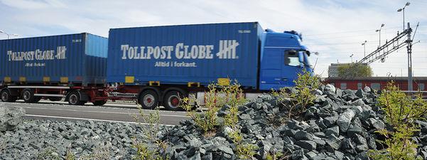 Foto av eit blått Tollpost-vogntog i fart langs vegen.