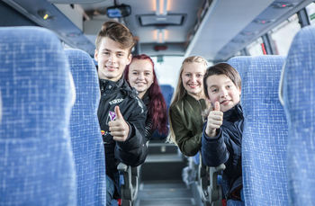 Foto som syner fire ungdomar, to jenter og to gutar, i ein buss. Alle smiler og gutane viser tommel opp-teiknet