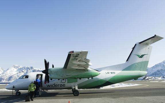 Foto av eit Dash 8-100 Widerøe-fly, som står parkert på rullebana. Det er folk på veg inn i flyet, og i bakgrunnen ser vi snødekte fjelltoppar.