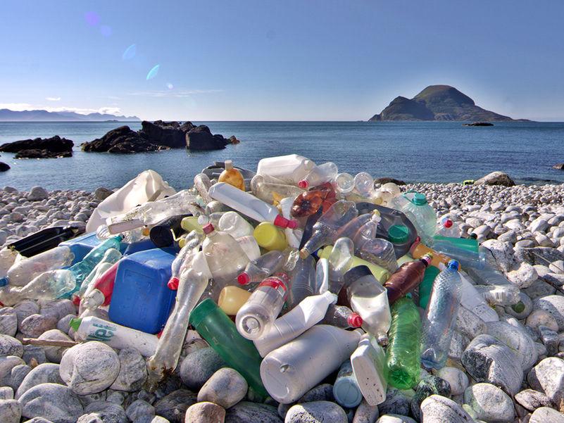 Foto som syner avfall, i hovudsak ulike plastflasker, langs kysten. Vi ser havet og øyer i horisonten, himmelen er blå.