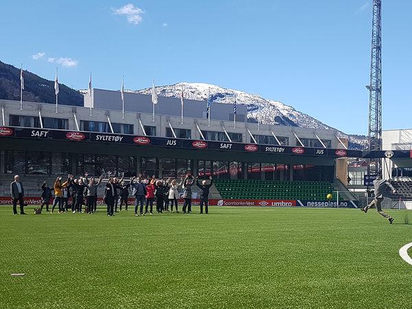 Foto frå oppstartssamlinga til det internasjonale prosjektet P-IRIS i april 2017. Biletet er frå Fosshaugane Campus i Sogndal, der deltakarane på samlinga er samla på bana. Ein av dei sparkar ein fotball mot dei andre, sparkar i gang prosjektet.