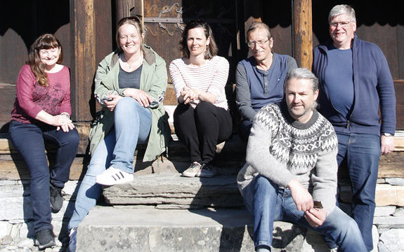 Foto som syner medlemane i verdsarvrådet for Urnes stavkyrkje på trappa framfor kyrkja. Biletet er teke i vårsola, og alle har sol i ansiktet.