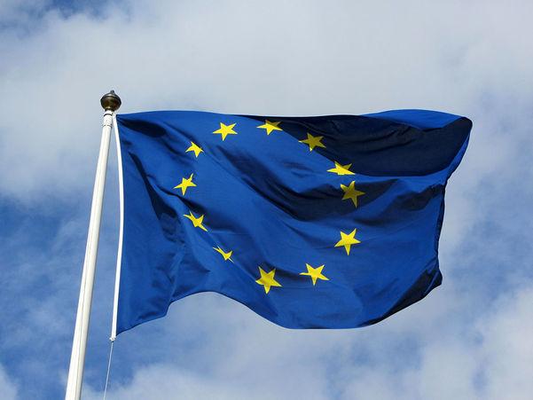 Foto av EU-flagget som vaiar mot blå himmel med litt skyer.