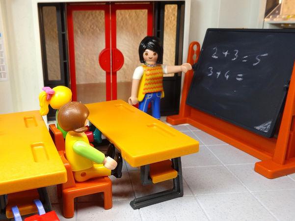 Foto som syner leikefigurane Playmobile i undervisningssituasjon. Ein figur står ved ei tavle, medan to sit ved pultane sine.