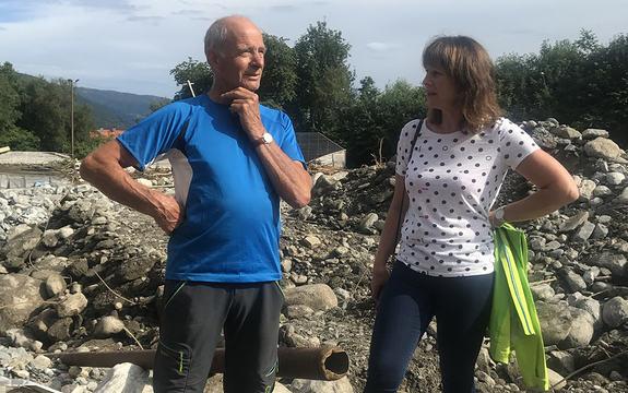 fylkesordførar Jenny Følling i flaumråka Utvik i samtale med innbyggar Mgne Sølvberg. bak dei ser i stein og tre og leire i eit tørt alternativt elveleie etter flaumen. sol og blå himmel.