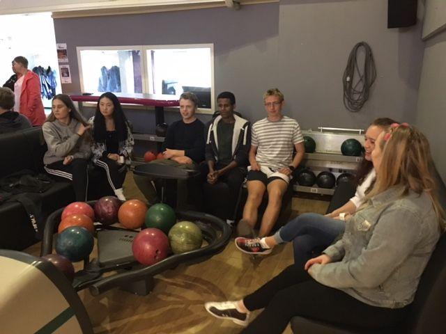 Ungdommar på benk i bowlinghallen.