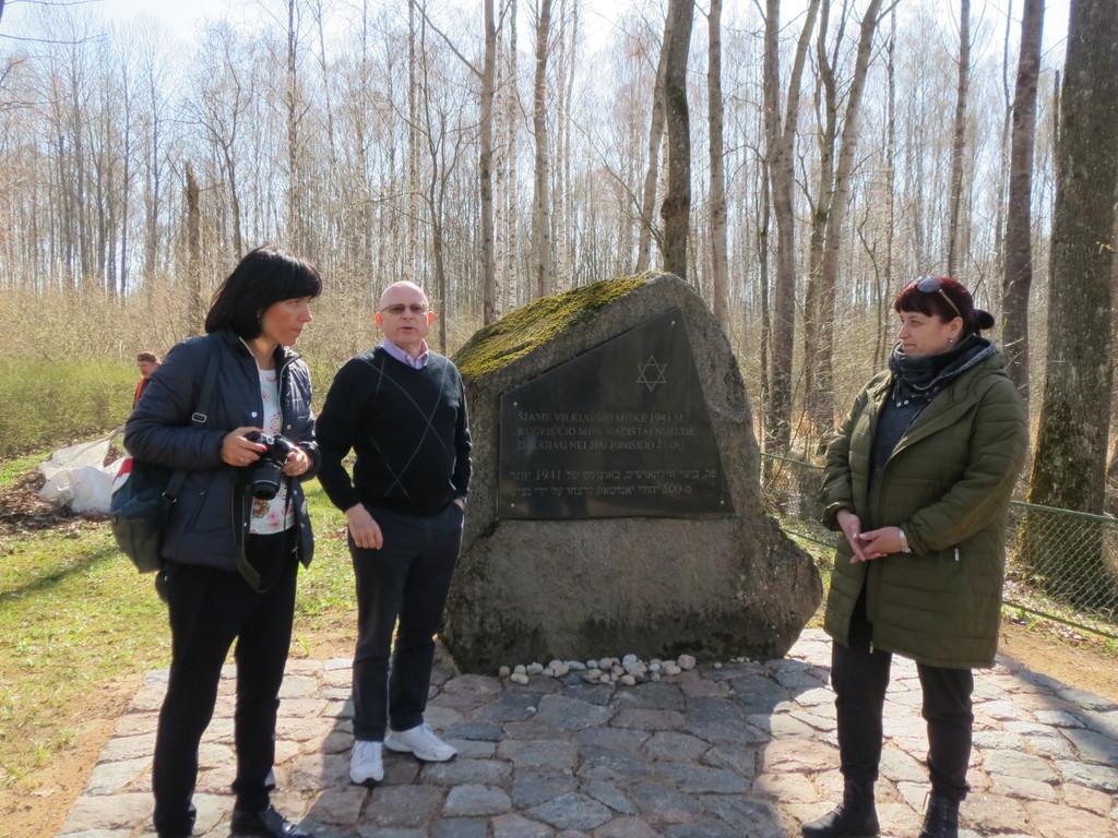 to damer og rektor Trygve foran et minnesmerke i stein