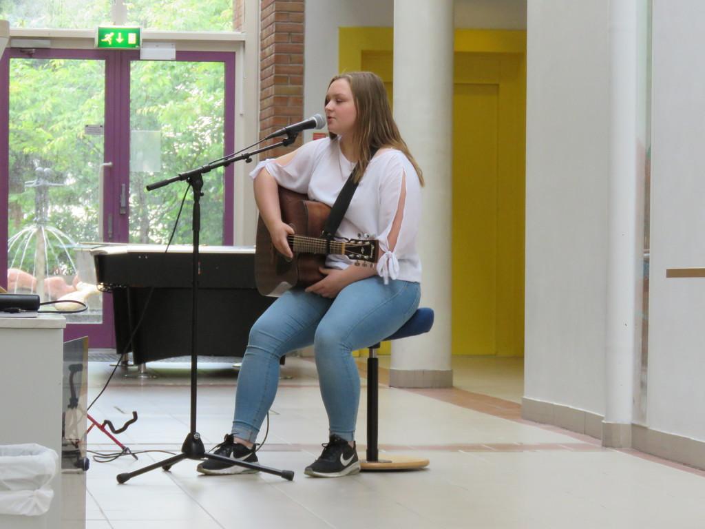 Synnøve skjærli sittande på ein stol med gitar, syng i mikrofon