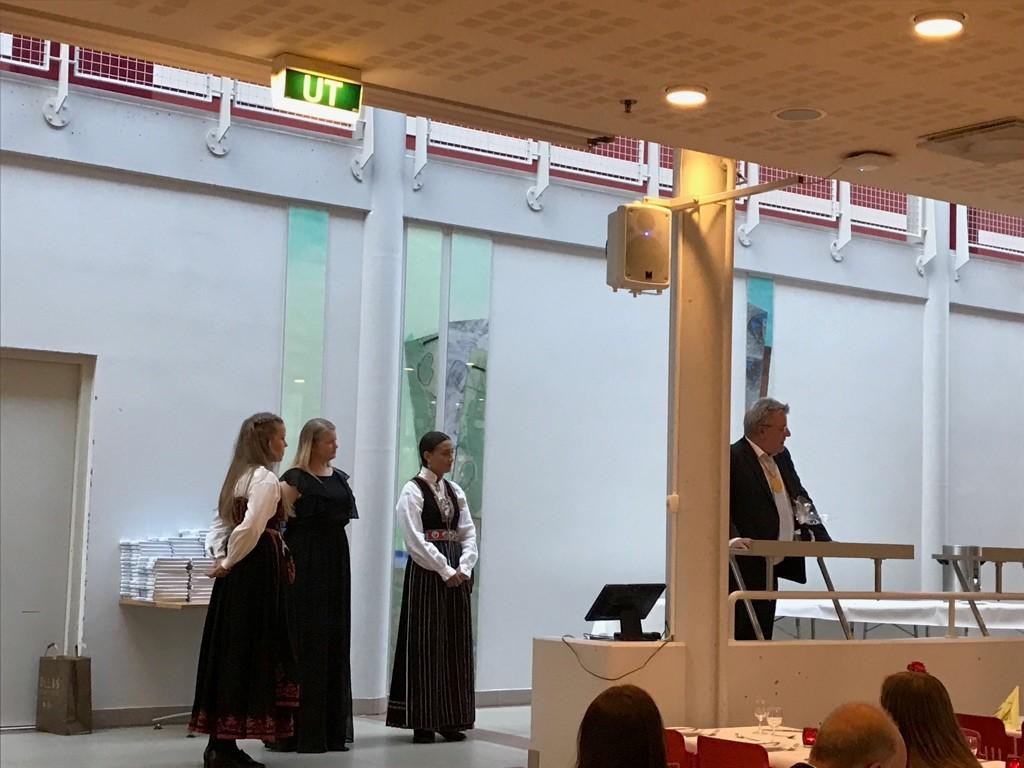 Rådgjevar Morten med mikrofon og tre jenter står foran resten av gjestene i kantina.