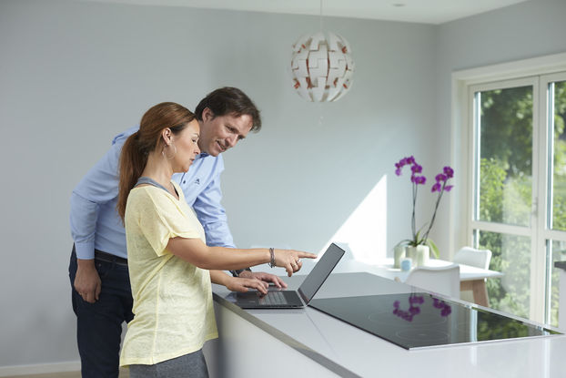 Dame peiker på dataskjerm og mann ser på, på kjøkkenet