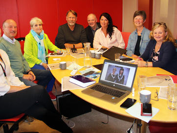 Ei gruppe tilsette i Sogn og FJordane og Hordaland fylkeskommunar sit rundt eit bord for å sjå på skisser av og bestemme fylkesordførarkjedet til Vestland fylkeskommune.