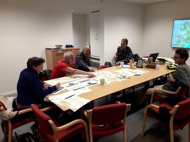 5 personar arbeider med kart rundt eit bord