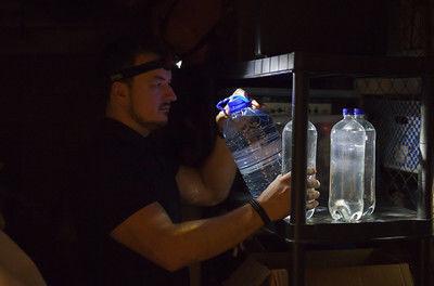 Mann i mørket med vannflaske